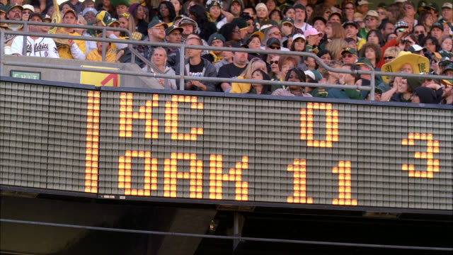 wide angle of scoreboard at baseball game indicating 'kc 0...oak 11.' sports. oakland 'a's' game against kansas city royals. '3' could indicate third inning. fans wearing oakland 'a's hats, caps, sweaters visible behind scoreboard. sports. - inning stock videos & royalty-free footage