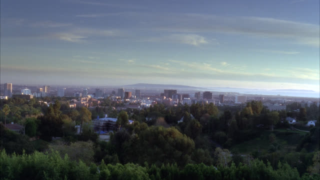 wide angle of city and skyline from mountain or hill. trees or woods visible in fg. could be century city. mountains visible in b g. - century city stock-videos und b-roll-filmmaterial