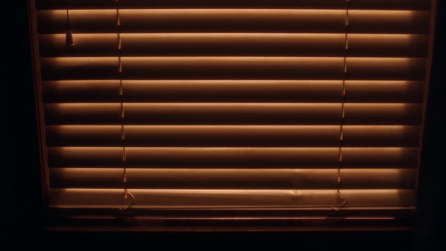 close angle of blinds going up in front of window. window sill in fg. - blinds stock videos & royalty-free footage