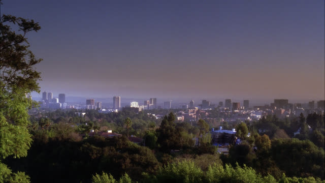 pan left to right across city skyline. century city visible. high rises, office buildings, and apartment buildings. trees in fg. houses visible. - century city stock-videos und b-roll-filmmaterial