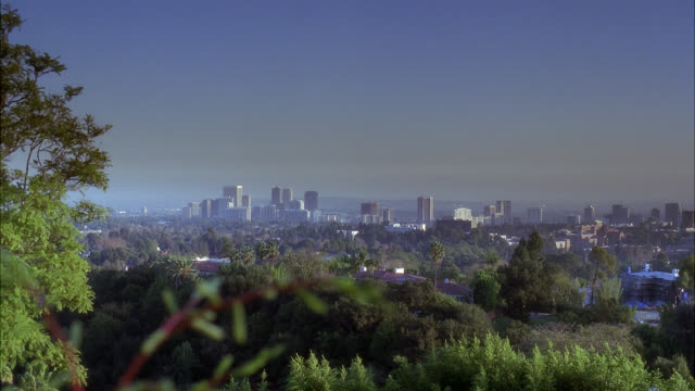 wide angle of city skyline. century city visible. high rises, office buildings, and apartment buildings. trees in fg. houses visible. - century city stock-videos und b-roll-filmmaterial