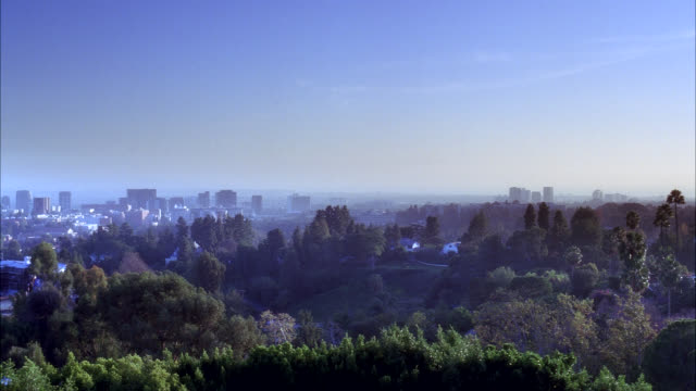 pan right to left and back of city skyline. century city visible. high rises, office buildings, and apartment buildings. trees in fg. houses visible. - century city stock-videos und b-roll-filmmaterial