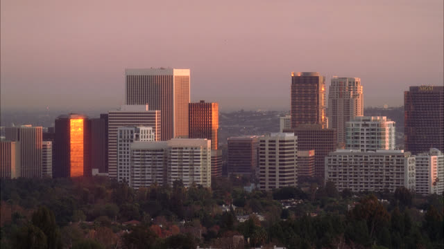 pan right to left from city skyline in santa monica to century and downtown los angeles. ocean visible in santa monica. high rise office buildings, skyscrapers, condominiums, and apartment buildings. us bank tower visible. houses  surrounded by trees visi - us bank tower stock videos & royalty-free footage