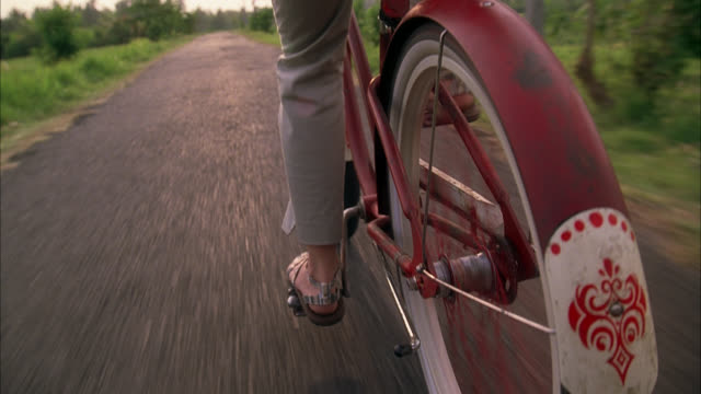 TRACKING SHOT, MEDIUM LOW ANGLE OF BICYCLE RIDING ON GRAVEL PATH OR NARROW ROAD ACROSS COUNTRYSIDE. POV FROM REAR, CLOSE ANGLE OF WOMAN'S FEET PEDALING ON VINTAGE BIKE. CLOSE SHOT OF FENDER AND SPOKES. WOMAN TAKES LEISURELY RIDE THEN STOPS ON LOOSENED GRA