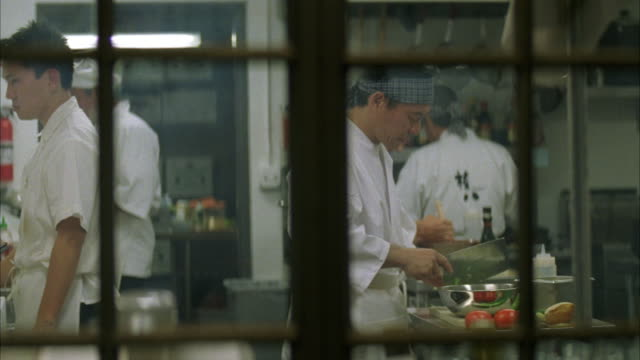 medium angle of sushi chefs in restaurant kitchen preparing meal. stove and ovens vile. men wear white coats. knives visible. chef hat. - chef's hat stock videos and b-roll footage