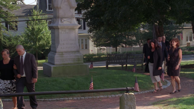 WIDE ANGLE OF PEOPLE WALKING ACROSS SMALL PARK NEAR SOLDIERS MONUMENT. AMERICAN FLAGS. COULD BE FOR FUNERAL. SMALL TOWN.