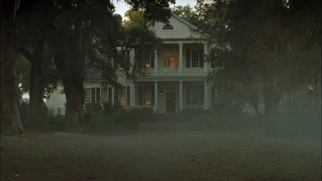 wide angle of two-story plantation home or mansion with large trees, pillars. smoke visible in fg. upper class, colonial period. - south carolina stock videos & royalty-free footage