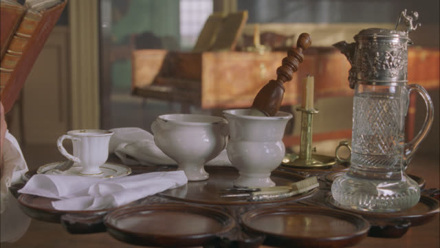 medium angle of colonial period shaving or grooming instruments. shaving brush, cups and saucers, candle, pitcher visible on vintage table. piano visible in bg. - shaving brush stock videos & royalty-free footage