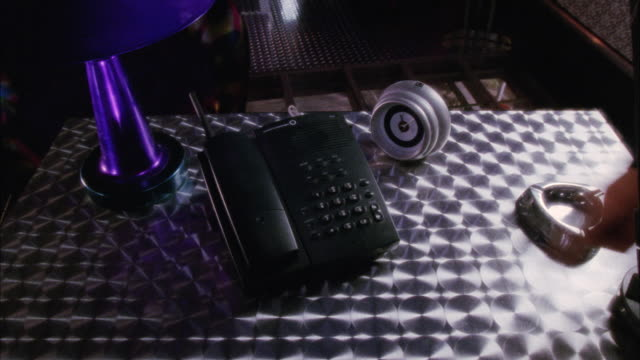 close angle of black telephone and answering machine sitting on metal table with ash tray and alarm clock next to it. man's hand comes in from right and pushes button on phone. flashing light in bg. series. - man and machine stock videos & royalty-free footage