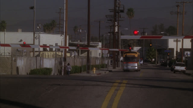 WIDE ANGLE OF BUS WITH STUNT MAN RIDING ON TOP APPROACHING TRAIN TRACKS. INDUSTRIAL AREA. RAILROAD CROSSING LIGHTS AND SWING-ARM GO DOWN AS TRAIN APPROACHES. TRAIN MOVES BY. WAREHOUSES IN BG.