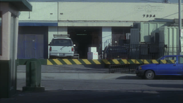 medium angle driving pov as car drives out of parking lot toward security guard shack and gate. delivery van pulls up in front, door opens to reveal man inside with machine gun. trap, ambush or attack. warehouses or auto repair shops in bg. - man and machine stock videos & royalty-free footage