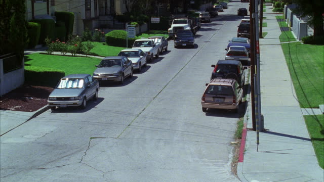 high angle down of street in middle class residential area or suburbs. cars parked. grass lawns and rose bushes in front yards. - 1999 stock videos & royalty-free footage