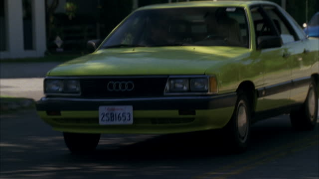 TRACKING SHOT CLOSE ANGLE OF YELLOW FOUR DOOR AUDI CAR DRIVING ON CITY STREET IN SUBURBS. COULD BE RESIDENTIAL AREA.