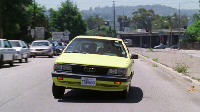 WIDE ANGLE OF YELLOW AUDI CAR DRIVING ON SUBURBAN STREET. CAR PASS BUSINESSES AND CHURCH. GAS STATION VISIBLE ON STREET CORNER. COULD BE CAR CHASE. YELLOW CAR SWERVES ON CITY STREET. DRIVER AND PASSENGER STRUGGLE FOR CONTROL OF WHEEL. COULD BE FIGHT OR ST