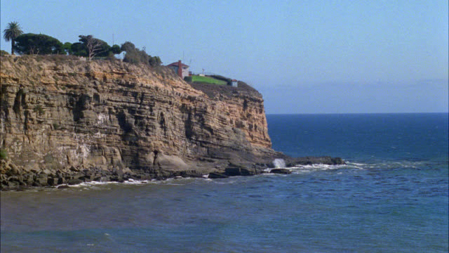 wide angle of bluff or cliff over ocean. could be palos verdes. trees and house visible overlooking ocean. - pazifikküste stock-videos und b-roll-filmmaterial