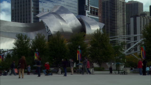 WIDE ANGLE OF DOWNTOWN CHICAGO, SKYSCRAPERS, MULTI-STORY BUILDINGS, MILLENNIUM PARK, CURVY SHEET METAL SCULPTURE OF FRANK GEHRY DESIGNED JAY PRITZKER PAVILION OUTDOOR CONCERT VENUE AND BEAN SCULPTURE WITH REFLECTIVE SURFACE.