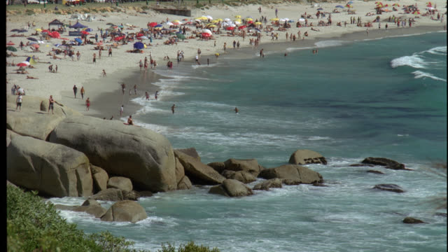vídeos de stock e filmes b-roll de high angle down of beach resort or vacation spot by ocean or large body of water. sand, people, vacationers, crashing waves, white caps, and large rocks. top of palm trees visible in fg. could be beach town. - 1995