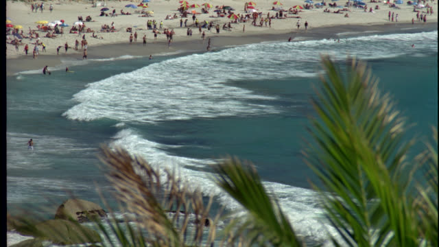 vídeos de stock e filmes b-roll de high angle down of beach resort or vacation spot by ocean or large body of water. sand, people, vacationers, rolling waves, white caps. top of palm trees visible in fg. could be beach town. - 1995