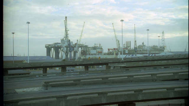 vídeos de stock e filmes b-roll de wide angle of cranes at a port or harbor. large boat or cargo ship visible. highway ramps or overpass in foreground with cars passing by. cloudy. - 1995