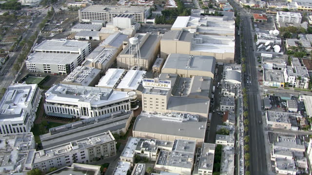 aerial of sony pictures studios lot. multi-story office buildings. sound stages. columbia pictures sign and billboard or advertisement. wheel of fortune. game shows. water tower. cities. los angeles area. - culver city stock videos & royalty-free footage