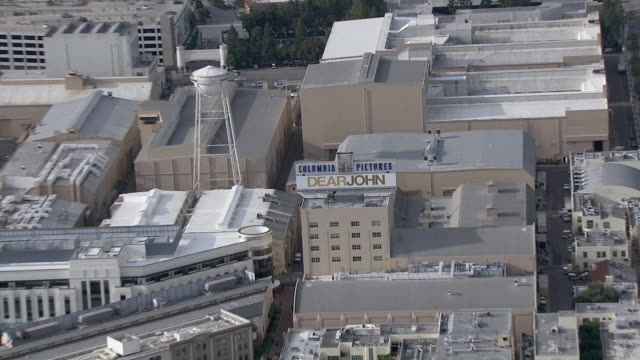 vídeos de stock e filmes b-roll de aerial of sony pictures studios lot. multi-story office buildings. sound stages. columbia pictures sign and billboard or advertisement. water tower. city streets. apartment buildings. parking garages. los angeles area. - culver city