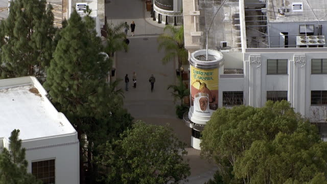 vídeos de stock e filmes b-roll de aerial of sony pictures studios lot, madison ave. gate or entrance. multi-story office buildings. sound stages. parking lot. pedestrians on main street. alleys. water tower. los angeles area. - culver city