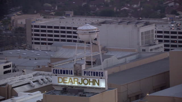 vídeos de stock e filmes b-roll de aerial of water tower on sony pictures studios lot. multi-story office buildings. sound stages. columbia pictures sign and billboard or advertisement. los angeles area. - culver city