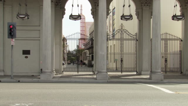 zoom in on iron gate or entrance behind colonnade on washington blvd of sony pictures studio lot. pillars or columns. los angeles area. - culver city stock videos & royalty-free footage