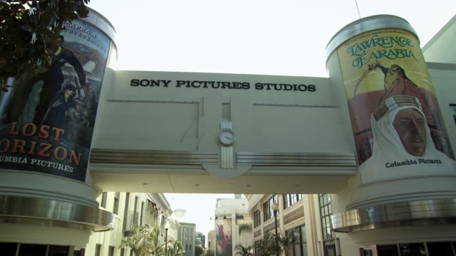 "vídeos de stock e filmes b-roll de pan down from ""sony pictures studios"" sign over main street. movie posters or signs for ""lawrence of arabia"" and ""lost horizon"". office buildings and storefronts. sony pictures studio lot. los angeles area. - culver city"