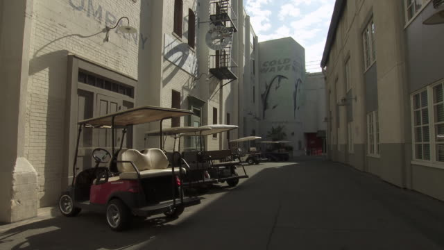 wide angle of golf carts parked in alley along multi-story painted brick building. could be office or apartment building. sony pictures studio lot. los angeles area. - culver city stock videos & royalty-free footage