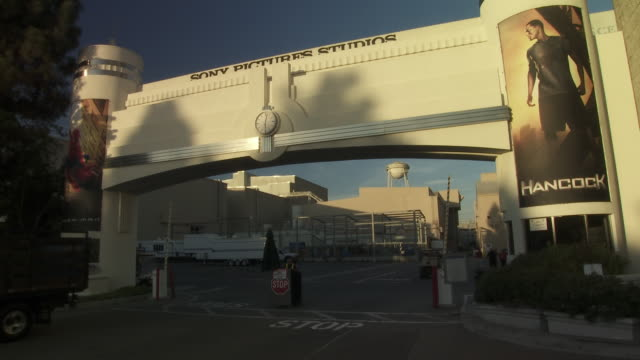 vídeos de stock e filmes b-roll de pan up of overland gate or entrance to sony pictures studio lot. security gates. los angeles area. - culver city