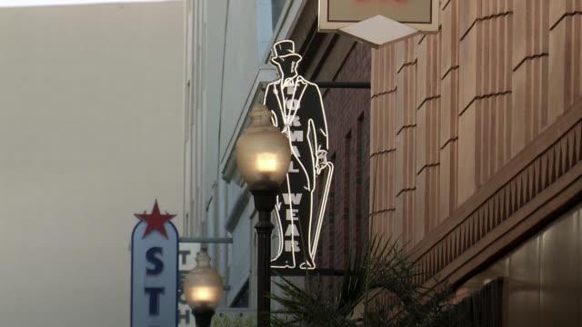 "zoom in on ""formal wear"" neon sign above storefront. main street. sony pictures studio lot. los angeles area. - targa con nome della via video stock e b–roll"