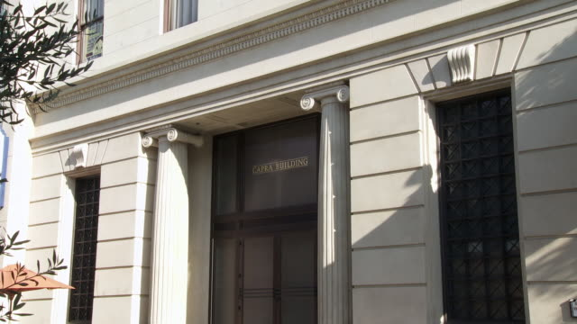 medium angle of capra office building. could be entrance or door to bank or government building. main street. sony pictures studio lot. los angeles area. - targa con nome della via video stock e b–roll