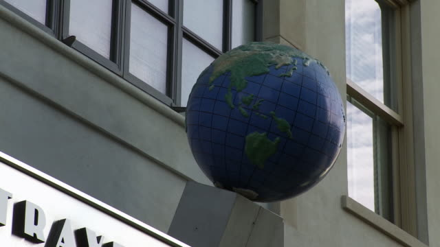 """close angle of globe on """"twentieth century travel"""" sign on storefront. could be travel agency. main street. sony pictures studio lot. los angeles area. - targa con nome della via video stock e b–roll"""
