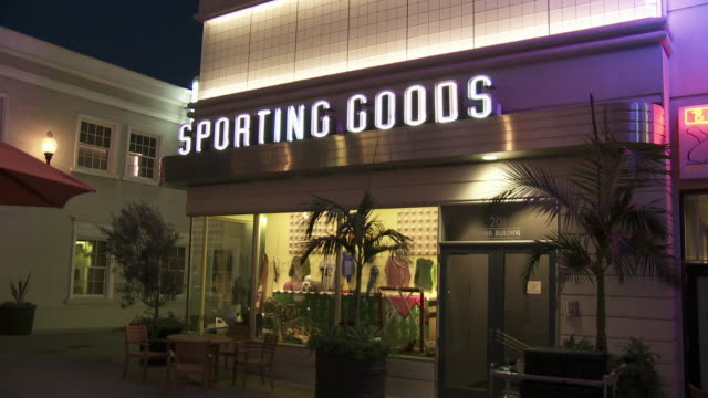 """wide angle of neon """"sporting goods"""" sign above window display on storefront. main street. sony pictures studios lot. movie studios. los angeles area. - targa con nome della via video stock e b–roll"""