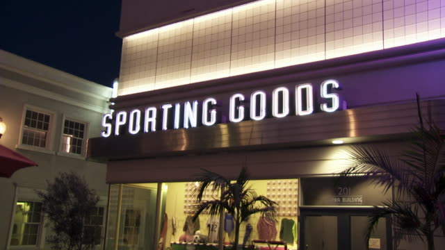 """zoom in on neon """"sporting goods"""" sign above window display on storefront. main street. sony pictures studios lot. movie studios. los angeles area. - targa con nome della via video stock e b–roll"""