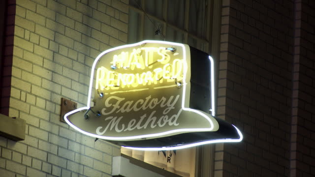 """vídeos y material grabado en eventos de stock de close angle of neon """"hats renovated"""" sign on brick building on main street. sony pictures studios lot. movie studios. los angeles area. - señal de nombre de calle"""