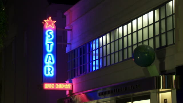 """wide angle of neon """"star line bus depot"""" sign on main street. could be station or terminal. """"twentieth century travel"""" storefront. could be travel agency. sony pictures studio lot. los angeles area. - targa con nome della via video stock e b–roll"""