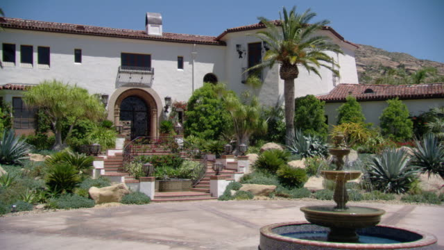wide angle of two story spanish or mediterranean style upper class house or mansion. garden and fountain. palm trees and cactus plants. desert. red tile roofs. - 2000s style点の映像素材/bロール