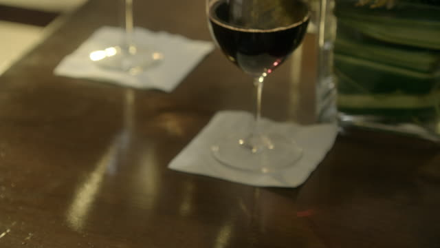 close angle of woman checking sony ericsson flip phone at table. wine glass and table out of focus in bg. camera zooms in on woman opening phone. series. - wine glass stock videos & royalty-free footage