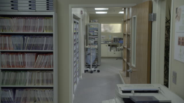 wide angle of file or records room of doctor's office. could be dentist office. fax and copy machine in fg. medical equipment visible in bg. could be any kind of doctor's office. blood pressure machine visible. - fax machine stock videos & royalty-free footage