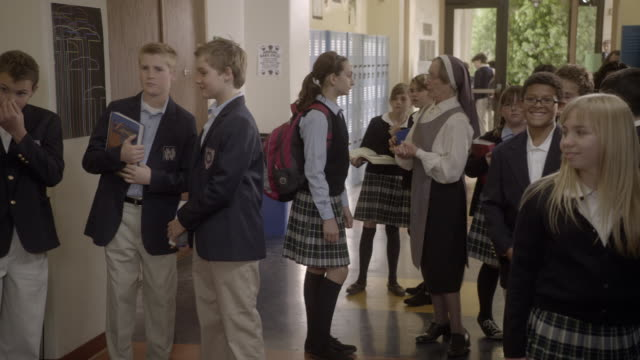 MEDIUM ANGLE OF MIDDLE SCHOOL CHILDREN IN HALLWAY OF CATHOLIC OR PRIVATE SCHOOL. NUN VISIBLE IN BG. CHILDREN DRESSED IN UNIFORMS GATHER IN FRONT OF CAMERA WATCHING. COULD BE FIGHT. LOCKERS VISIBLE.