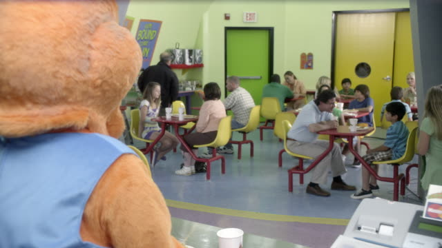 medium angle of children's restaurant or  family restaurant. families sit at tables visible in bg. cash register and person in animal costume visible in fg. tray with food. - animal costume stock videos & royalty-free footage