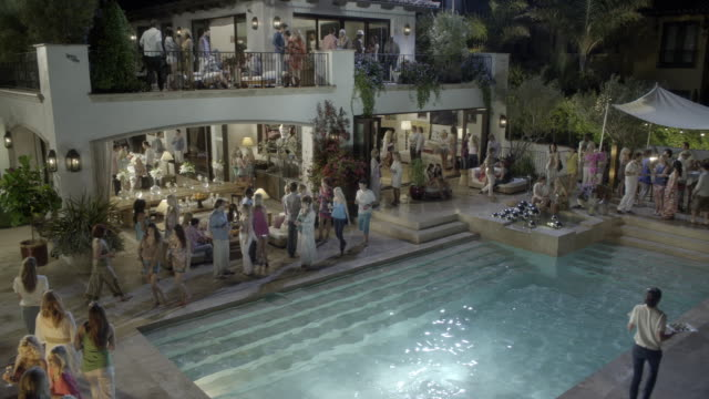 high angle down of upper class party at multi-story mansion, estate, or house. people visible on outdoor lounge or patio area. balcony area. people walk around with wine and lounge on chaise couches. living room visible in bg. swimming pool visible in fg. - exclusive stock videos & royalty-free footage