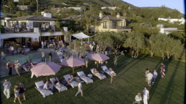 high angle down of upper class party at multi-story mansion, estate, or house overlooking ocean and beach. could be malibu and pacific coast. people visible on lounge chairs under umbrellas and in swimming pool. balcony area. people walk around with wine - malibu stock videos & royalty-free footage