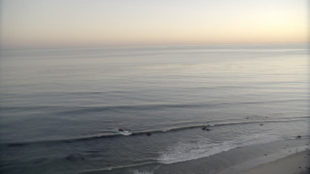 pan left to right from stairs on bluff or cliff leading to beach or ocean. to white angle of ocean at sunset. could be pacific coast. could be malibu. - pacific coast stock videos & royalty-free footage