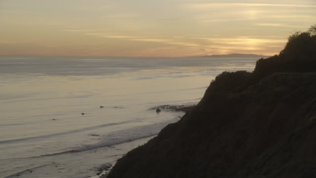 wide angle of bluff or cliff and ocean at sunset. could be pacific coast. could be malibu. island visible in bg. c could be catalina. - pacific coast stock videos & royalty-free footage
