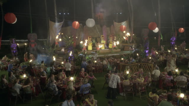 stockvideo's en b-roll-footage met high angle down of luau at hotel or resort. stage with male and female hawaiian hula dancers and torch throwers. chinese lanterns hang over guests sitting and eating at tables. tiki heads and torches visible. performances. - tiki torch
