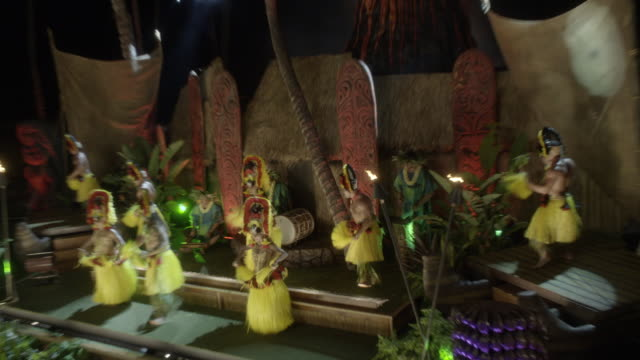stockvideo's en b-roll-footage met high angle down of luau with traditional hawaiian hula dance and torch twirling performance. men and women on stage. tiki heads and torches visible. guests or spectators partially visible. canted angle back and forth. - tiki torch