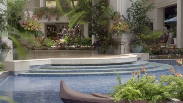 medium angle of fountain in lobby area of grand wailea hotel and resort. decorative stone boat with flowers visible. tropical plants visible in bg. guests with children visible in bg. - lobby stock videos & royalty-free footage